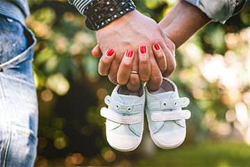 Couple holding hands and tiny shoes